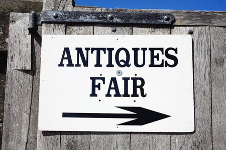 Antique sign directing buyers to an outdoor antiques retail fair photo