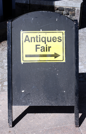bric: Antique sign directing buyers to an outdoor antiques retail fair Stock Photo