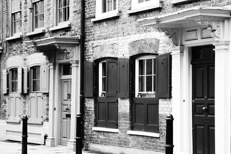 east end: Black  White image of Georgian terraced town houses in Spitafields in the East End of London, England, UK, which where the homes of wealthy Huguenot silk merchants escaping religious persecution in France Stock Photo