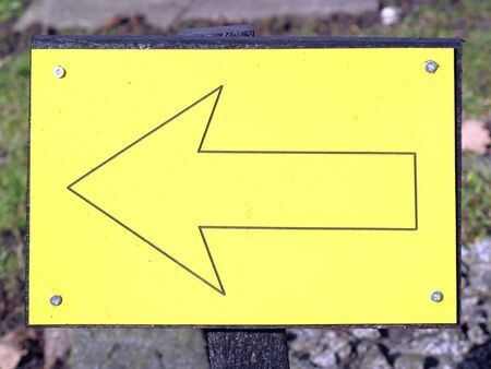 this: Metal yellow direction arrow sign pointing this way left Stock Photo