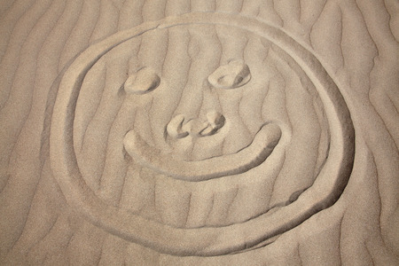 coastline: Background of a smiley face drawing on a coastline sand beach Stock Photo
