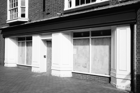 old building facades: Black  white image of a bankrupt closed down retail shop, with whitewashed windows, at a pedestrian shopping centre Stock Photo
