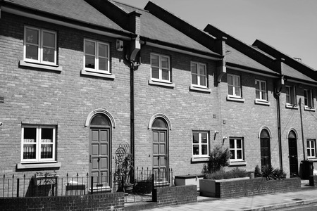 Black and white image of modern new terraced houses in Docklands, London, England, UK