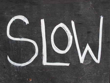 slower: Wooden old distressed blackboard slow sign background
