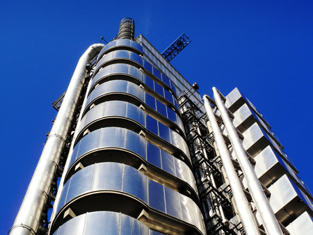 british english: The Lloyds Building in the heart of the financial district of London, England, UK, is the headquarters of the insurance firm Lloyds Of London