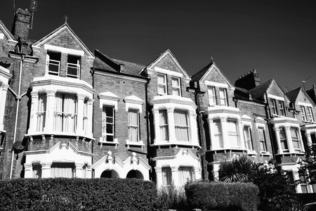 terraced: Black and white image of old fashioned typical Victorian terraced town houses architecture in London, England, UK. These residential homes are often turned into apartment flats