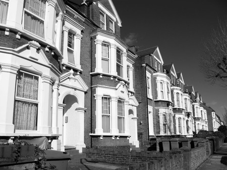 victorian architecture: Black and white image of old fashioned typical Victorian terraced town houses architecture in London, England, UK. These residential homes are often turned into apartment flats