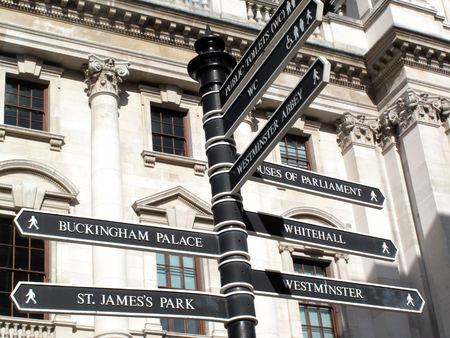 buckingham palace: Retro street signpost giving directions to Westminster Abbey, Houses of Parliament, Buckingham Palace, St Jamess Park, Whitehall and Westminster in London, England, UK Stock Photo