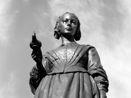 Black and white image of the Victorian memorial statue of Florence Nightingale 1820-1910 in London, England, UK who was an English nurse known as 'the lady with the lamp, who cared for wounded soldiers in the Crimean War