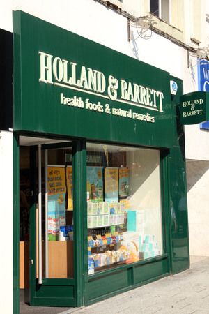 barrett: Cardiff, Wales, UK, September 14, 2016 :  Holland & Barrett logo advertising sign outside its retail  store in Queen Street Editorial