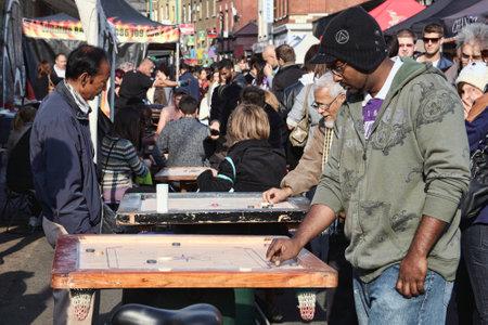 vintage: Londen, Verenigd Koninkrijk - 23 oktober 2011: De klanten het spelen van een Corrom tafel spel bij een marktkraam in Brick Lane straat vlooienmarkt