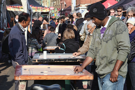 playing the market: London, UK - October 23, 2011:  Customers playing a Corrom table game at a market stall in Brick Lane street flee market