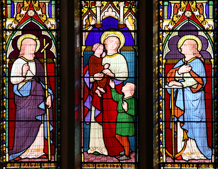 the gospels: Carmarthen, Wales, UK, October 22, 2016 :  Faith Hope Charity images on a stained glass window at St Peters Church in the city centre Editorial