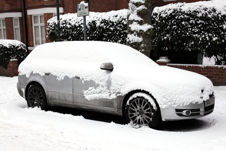 standstill: London, UK, December, 19 2010: A heavy snow fall covering a car in a Kilburn street bringing transport to a standstill