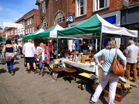 winchester: Winchester, UK - July 31, 2015:  Customers looking at antique and bric a brac stalls at the weekly street market in the city centr Editorial