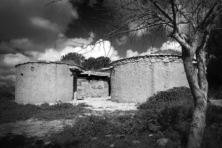 Reconstruction of houses of the Chalcolithic Period (Bronze Age) 3500BC at Lempa Experimental Village in Cyprus black and white monochrome image