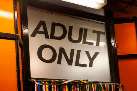 Adult only neon sign advertising an adult licensed sex shop cinema in a city red light district industry, stock image photo