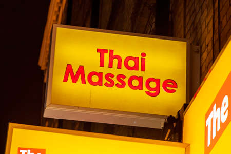 Thai massage sex shop neon sign advertising an adult licensed business in the Soho red light district industry, stock image photo