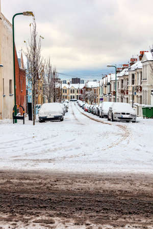 Street winter cityscape with snow terraced houses and frozen cars after a blizzard snowfall in London England UK, stock photo image with copy space