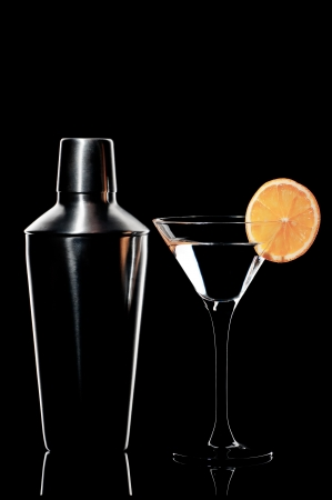 vodka: Shaker and cocktail in martini glass on a black background