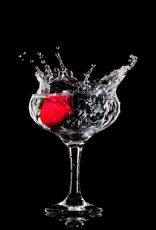 gin: fresh splashing strawberry into a wet cocktail glass