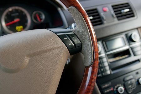 luxury car interior with wooden steering wheel close up photo