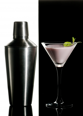 Metal cocktail shaker and cream cocktail with mint leaves on a black and white  background photo