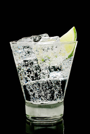 Sparkling water with ice cubes and piece of lime in old fashion glass on a black background photo