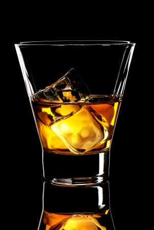 old fashion glass of whiskey with ice cubes on a black background photo