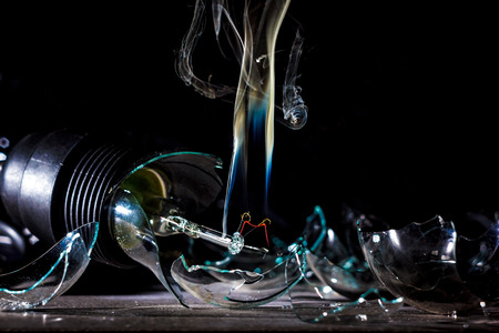 amazing explosion of a burning light bulb with splinters and smoke on a black background with a flash Stock Photo