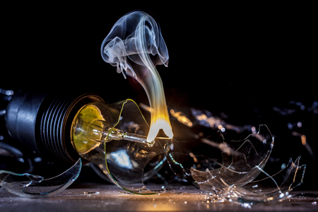 amazing explosion of a burning light bulb with splinters and smoke on a black background with a flash