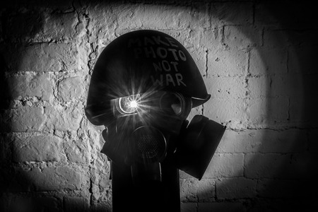 art picture of a military gas mask on a white brick wall with shadows with flash with the inscription make photo not war on Fatherland defender day Reklamní fotografie