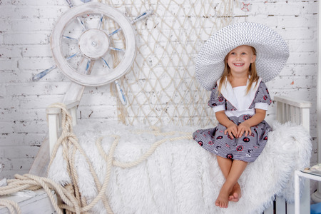 Portrait of one cute and mischievous european girl in a sea style studio on a white brick wall background