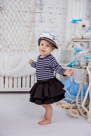 Portrait of a cute and naughty european little girl in a sailors clothing in the studio of marine style on a background of white brick wall Imagens