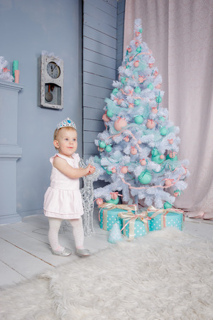 Portrait of a cute little european blond princess girl with a crown  in a beautiful dress in a studio decorated in the Christmas theme with toys and christmas tree