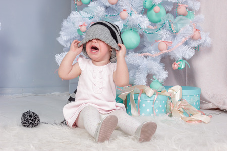 Portrait of cute little crying Princess girl in beautiful dress and striped hat sitting in studio decorated in christmas theme with toys, christmas tree and gifts