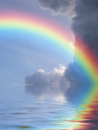 Rainbow reflected in ocean against a background of clouds
