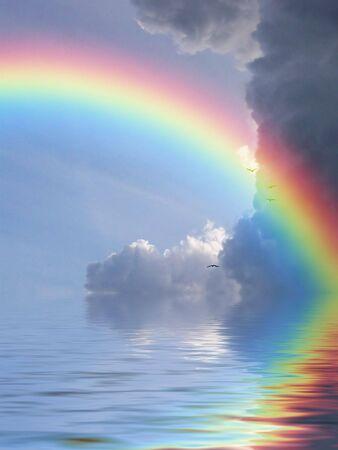 Regenbogen reflektierte sich im Ozean gegen einen Hintergrund der Wolken Standard-Bild