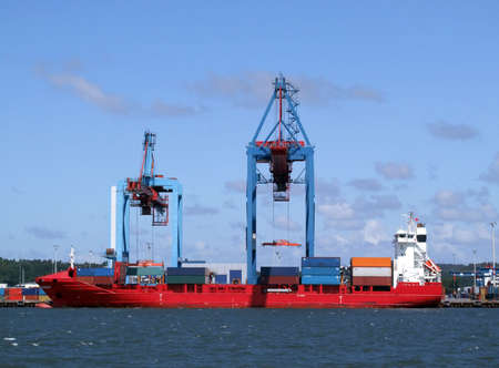 cargo ships being loaded and unloaded with containers in Gothenburg harbour by huge industrial cranes photo