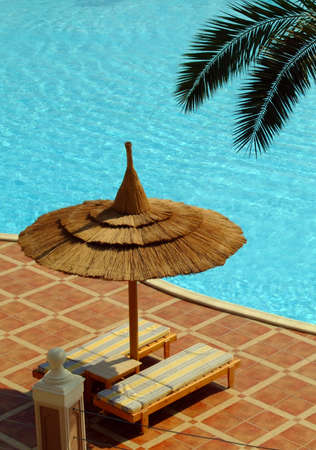 A parasol and loungers by a hotel poolside