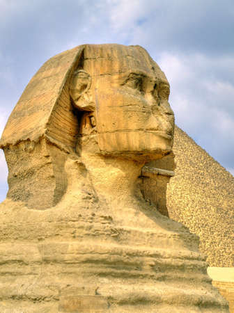 The sphinx of giza with a pyramid in the background Stock Photo