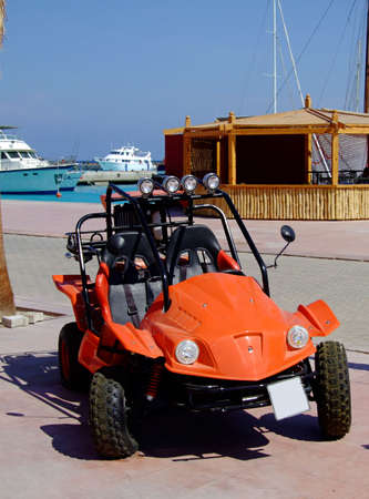 hobby hut: An orange beach buggy parked at a marina with luxury yachts in the background