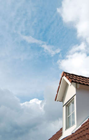 dormer: A second floor dormer window situated on a house roof against a heavenly sky background.