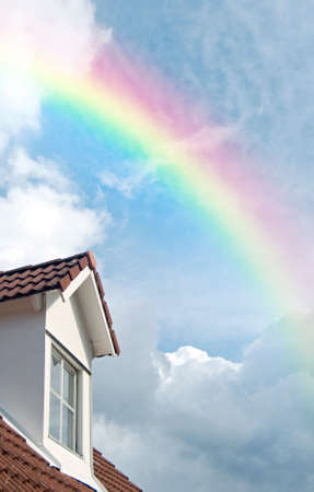dormer: A second floor dormer window situated on a house roof against a heavenly sky background with rainbow.