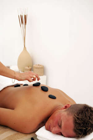 A young man relaxes as he enjoys a luxurious spa treatment from a female masseuse. Stock Photo - 5344912