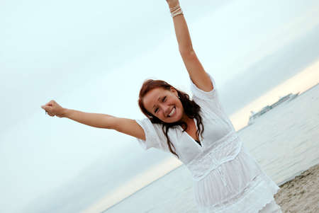 arms in air: A beautiful, fit and healthy young woman throws her hands in the air in a fit of joy. Stock Photo