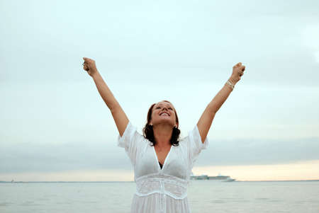 with raised: A beautiful, fit and healthy young woman throws her hands in the air in a fit of joy. Stock Photo