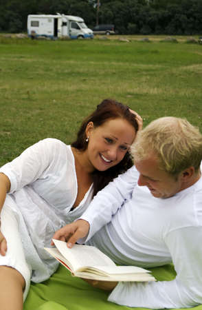 A young man reads poetry to his beautiful partner during a romantic picnic photo
