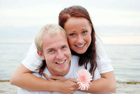 A handsome young man with his beautiful female partner holding a flower as they have fun by the beach. photo