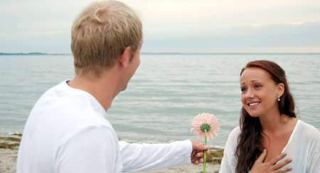 anniversary beach: A handsome young man gives his beautiful female partner a flower on their anniversary by the beach. Stock Photo
